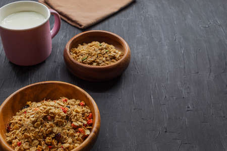 On a black background in wooden bowls lie muesli of two kinds, as well as one mug with cows milk Banco de Imagens