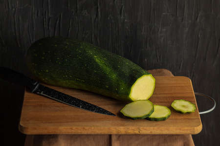 The horizontal photo shows an image of the cooking process. Three round slices are cut off from the whole courgette. Nearby is a ceramic knife. Objects lie on a wooden board
