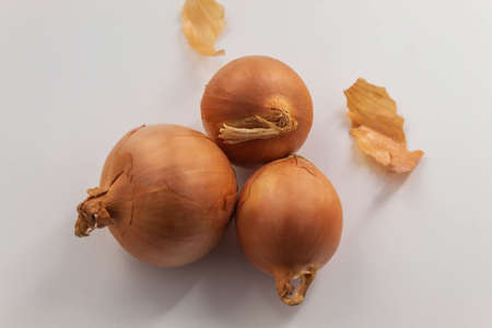 The horizontal photo shows food of the same species. It's onion. It's clean, husky and whole. Small onion on a white background close-up Banco de Imagens