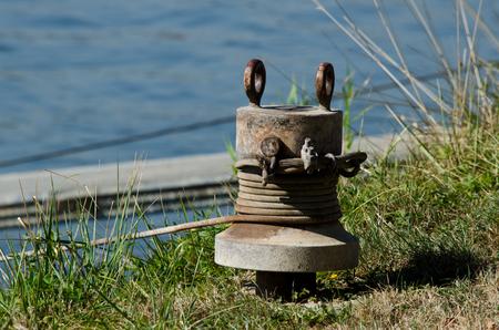 An old rusty bollard near by a dock. Stock Photo