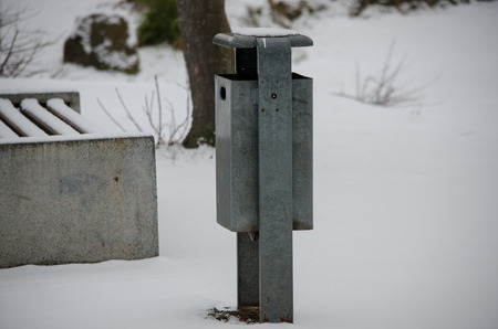 A galvanized trashcan standing in the snow, surrounded by trees and benches