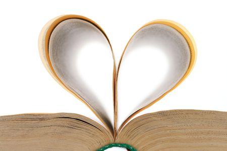 heart shape made from the leaves of the open book on white background photo