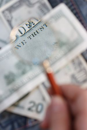 The back side of the one hundred U.S. dollars banknote is under the examination of the handheld magnifying glass photo