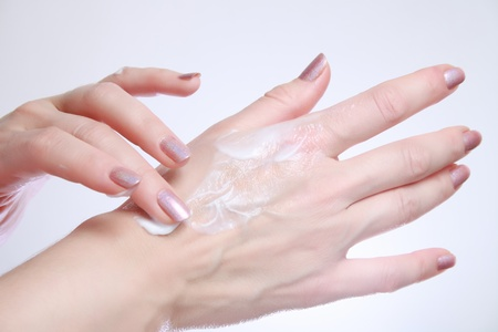 Woman applying moisturizing cosmetic creams on her hands with dry skin