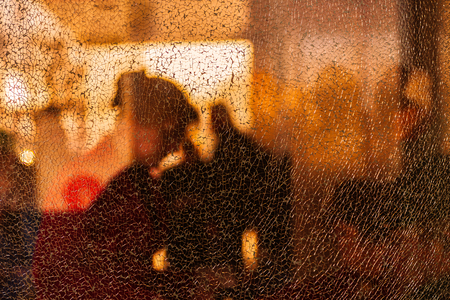 Blurred silhouettes of people behind broken glass. Fine mesh of cracks. Creative background. Female profile. Bus stop. Broken hopes. Diffused light. Stock Photo