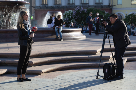 MOSCOW, RUSSIA - May 21, 2018: The film crew of the Bulgarian TV channel Kanal 3 shoots a report near the Bolshoi Theater. A woman is a journalist with a microphone and a cameraman with a camera. The microphone has a red logo.