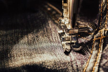 Repair jeans on the sewing machine. View of the fabric, needle and thread. Illumination from the built-in incandescent lamp. Jeans are a type of trousers, typically made from denim or dungaree cloth Archivio Fotografico