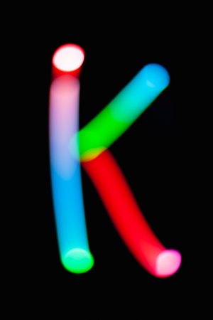 Letter K. Glowing letters on dark background. Abstract light painting at night. Creative artistic colorful bokeh. New Year. Use it for build you own design for book cover, CD, poster or post card. Stok Fotoğraf