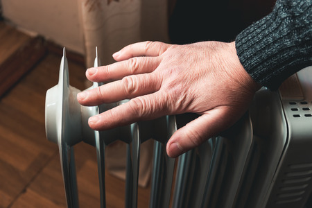 A man checks the temperature of an electric oil heater with his hand. In the off-season, central heating does not always work. Additional heaters needed to keep house warm. Electricity bills increased