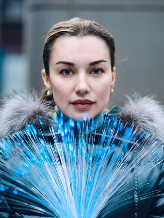 Portrait of young woman with a bunch of glowing optical fibers in her hands looking at camera. Concept of global new telecommunication technology. Fast data transfer. Virtual networking. Copy space.