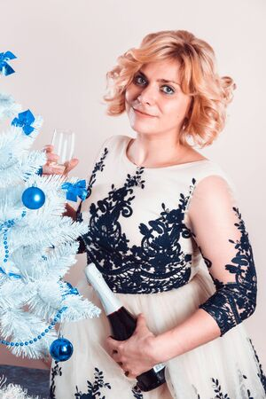 Young happy woman with bottle and glass of champagne in hands in elegant evening dress stands near white artificial Christmas tree with blue glass balls toys.