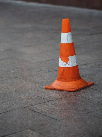 Orange plastic safety cone with strips of retro reflective film on the sidewalk paved with granite tiles in Moscow, Russia.