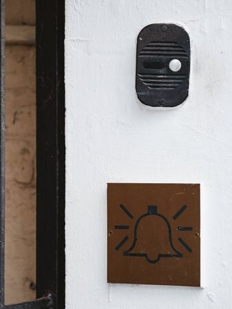 The intercom on the white wall of the house and the emblem with a bell icon. Intercom with a call button and a plate with a bell picture. Call communication device to enter into apartment building.
