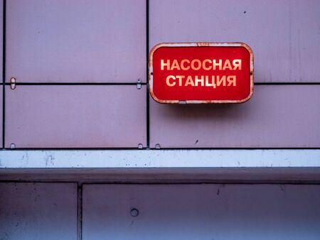 Red industrial plate with light on the wall of the building above the entrance to the basement with the inscription in Russian - Pumping Station. Moscow, Russia.