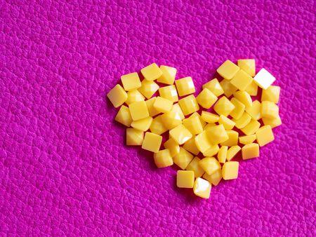Artesanía de cristal amarillo en forma de corazón hecho a mano para bordado de diamantes con diamantes de imitación. Fondo con textura de cuero brillante. Pieza rosa de piel de becerro curtida natural pintada y tratada. Disparo de lente macro