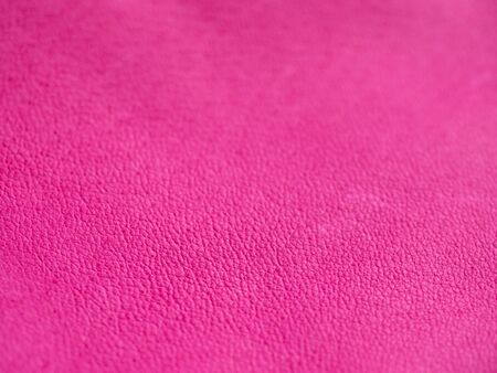 Background with leather texture. Pink piece of natural tanned calfskin painted and treated with fuchsin paint. Shallow depth of field, shot from side with macro lens. Copyspace for border or frame