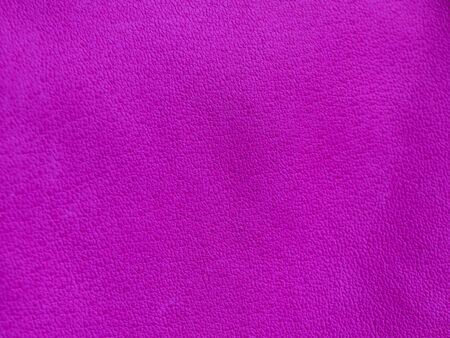 Background with leather texture. Violet piece of natural tanned calfskin painted and treated with fuchsin paint. Lots of detail, frontal shot with macro lens. Copyspace for border or frame