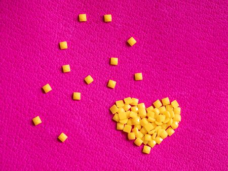 Yellow crystal craft handmade heart shape for diamond embroidery hobby rhinestone. Background with bright leather texture. Pink piece of natural tanned calfskin painted and treated. Macro. Copyspace