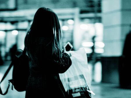 Blurred unrecognizable figure of a young girl hurrying down street in dark coat and a mobile phone in her hands. Stylized silhouette of a young modern woman with a backpack and a package in her hands Zdjęcie Seryjne