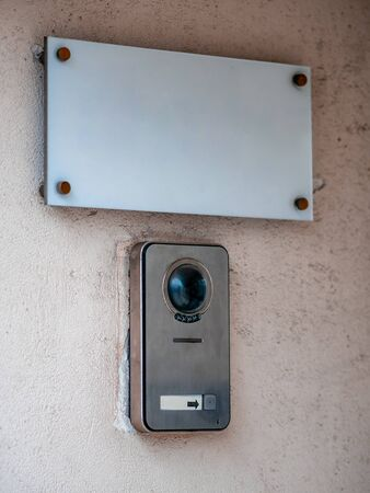 A sign board on  wall of the building and a call button for staff. White rectangular plate with a bell and cctv intercom. Blank for your text. Mockup empty template