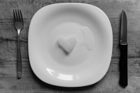 A snowy heart melts on a white plate. Heart shaped snow on a saucer. Ice in frosty weather. Melted water is collected in a small puddle. Wooden background. Love on valentine's day concept Banco de Imagens