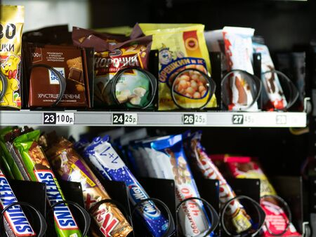 Moscow, Russia - February 8, 2020: Chocolate bars Snickers, Twix, Milky Way, snacks, cookies and nuts in a transparent glass window of a vending machine.