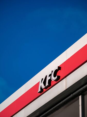 Moscow, Russia - February 8, 2020: Signboard of a fast-food restaurant KFC - an international chain of catering restaurants. Kentucky Fried Chicken logo on a building facade against a bright blue sky.