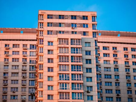 Moscow, Russia - February 8, 2020: Facade of a high-rise apartment building near the MCD Begovaya railway station at sunset. Modern building illuminated by the rays of the setting sun against blue sky
