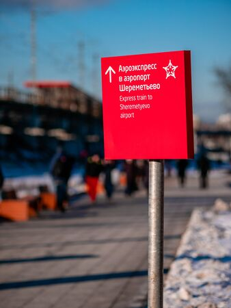 Moscow, Russia - February 8, 2020: People walk near Okruzhnaya station of Moscow Central Diameter (MCD). Red sign with pointer to Aeroexpress to Sheremetyevo airport which is shared the same railway. Editorial