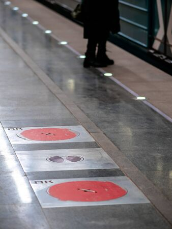Fire hatches at the Moscow metro station. Red covers on the floor of the platform at the wells with fire hydrants in the subway
