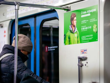 Moscow, Russia - February 8, 2020: A man rides in a subway car next to an Delivery Club advertisement. A young man stands at door of subway train. Poster invites to work as couriers for food delivery Editorial