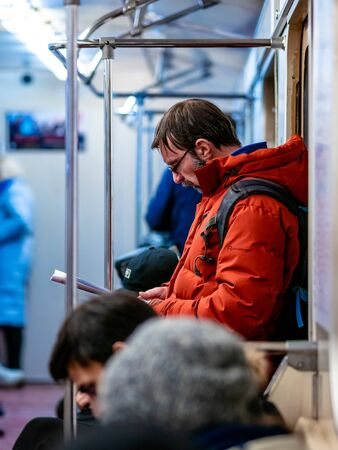 Moscow, Russia - February 8, 2020: Man rides in subway car and reads a magazine. Guy with glasses and orange jacket is standing at door of subway train with book or printout of article in his hands. Editorial