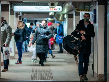 Moscow, Russia - December 6, 2019: Man with N95 class face mask respirator in passage near entrance to the Novye Cheryomushki metro station. Man expects someone in a virus protective mask in underpass