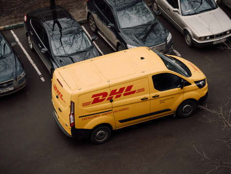 Moscow, Russia - March 11, 2020: DHL Deutsche Post courier in yellow-red uniform near minivan with company logos. DHL International GmbH is world largest courier, parcel, and express mail service