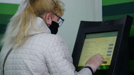 Dnipro, Ukraine - March 27, 2020: Woman in black protective mask and disposable gloves at Privatbank ATM. City has been quarantined. Due to threat of spread of coronavirus emergency state is declared