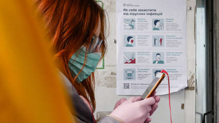 Dnipro, Ukraine - March 27, 2020: Lady in medical mask and gloves rides in trolley bus. Safety leaflet from COVID-19 in background. Due to threat of spread of coronavirus emergency state is declared