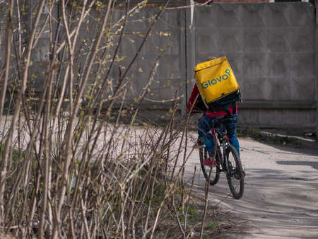 Dnipro, Ukraine - March 27, 2020: GLOVO delivery woman courier on bike with branded yellow thermal backpacks deliver customer orders. City has been quarantined due to threat of coronavirus pneumonia Editorial