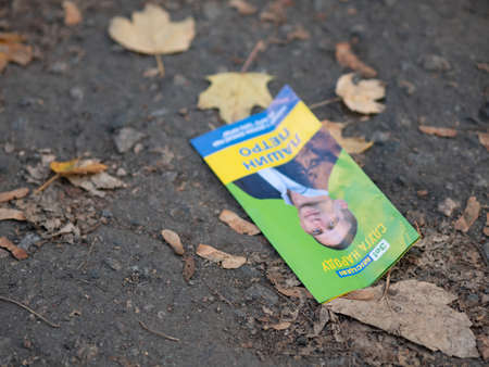 Dnipro, Ukraine - October 23, 2020: A leaflet thrown on the street of the city before the elections of local deputies. Advertising of the deputy of the Sluga Naroda party, Ze! on the eve of the vote Editorial