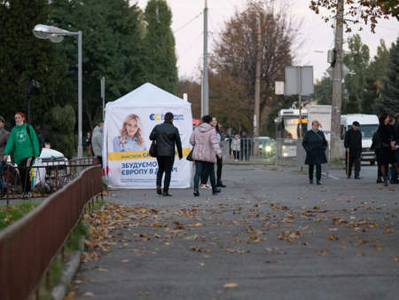 Dnipro, Ukraine - October 23, 2020: Agitators hand out leaflets at campaign cubes ahead of parliamentary elections. Lady with printed promotional materials for European Solidarity party on eve of vote