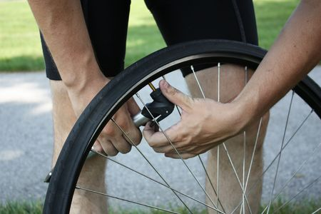 Adult male inflating tire  Stock Photo