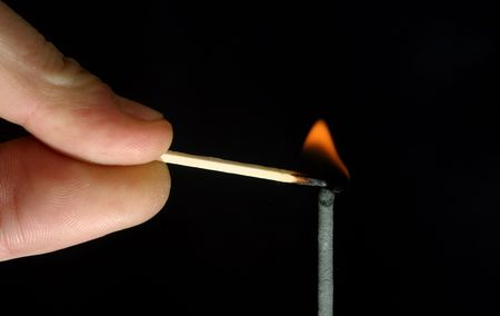 head start: Man lighting a fuse with a safety match Stock Photo
