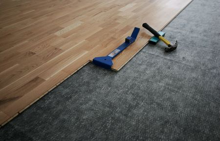 Laying down a laminated wooden floor Stock Photo