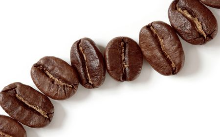 decaf: coffee beans isolated on a white background. Extreme close-up