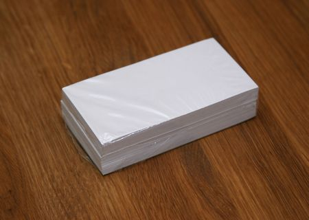 Plastic wrapped business cards on a wooden table photo