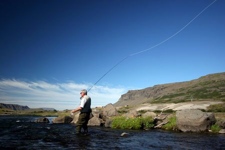 trout fishing: Flyfisherman casting in a salmon river