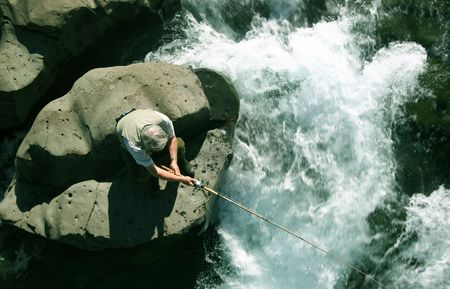 Old man fishing in a salmon river photo
