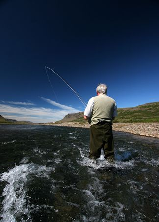iceland: Fisherman standing in river with a fish on the line Stock Photo