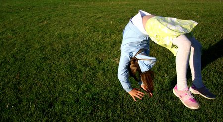 midair: Girl in mid-air doing somersault on green grass