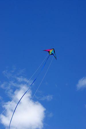 papalote: Colorido cometa vuela alto en el fuerte viento  Foto de archivo