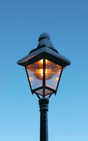 Vintage streetlamp covered with frost and snow photo